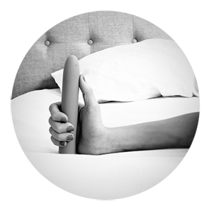 woman holding a vibrator in bed
